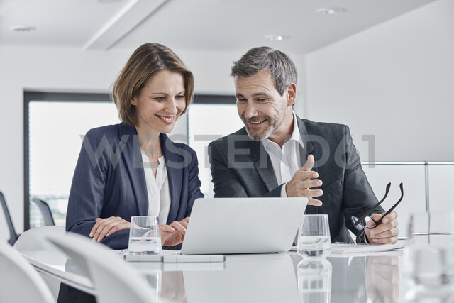 Businessman and businesswoman having a meeting in office with laptop - RORF01352 - Roger Richter/Westend61