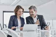 Businessman and businesswoman having a meeting in office with laptop - RORF01352
