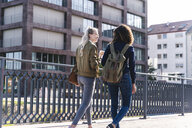Friends walking on bridge, talking, having fun, rear view - UUF14155