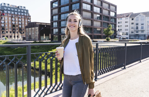 Young woman walking on bridge, drinking coffee, listening music with headphones - UUF14158