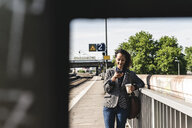 Young woman at train station reading text messages on her phone - UUF14164