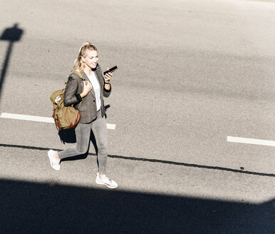 Young woman walking on empty road, talking into her smartphone - UUF14173