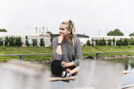 Young businesswoman sitting outdoors, taking a break - UUF14203