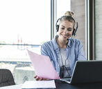 Young businesswoman sitting at desk, making a call, using headset and laptop - UUF14233