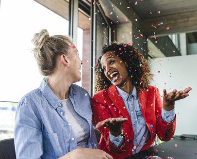 Young busniesswomen celebrating success, throwing confetti - UUF14239