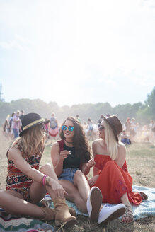 Young people sitting on blanket at music festival - ABIF00594