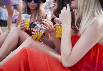 Friends drinking juice and sitting on meadow during music festival - ABIF00597