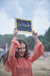Woman holding sign at music festival, freedom - ABIF00609