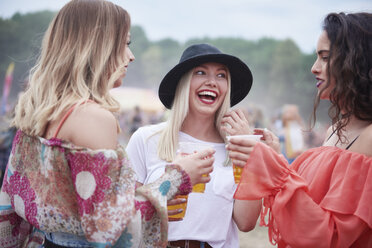 Friends drinking juice and sitting on meadow during music festival - ABIF00612