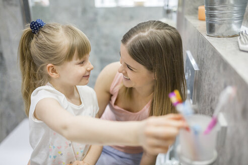 Mother and daughter brushing teeth in bathroom - AWF00066