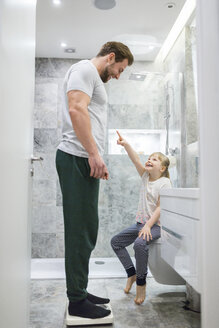 Father and daughter checking weight on bathroom scales - AWF00090