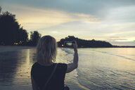 Thailand, Khao Lak, back view of woman taking photo with cell phone on the beach at sunset - CHPF00481