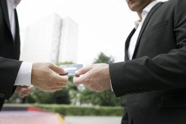 Two businessmen handing over credit card - KMKF00379