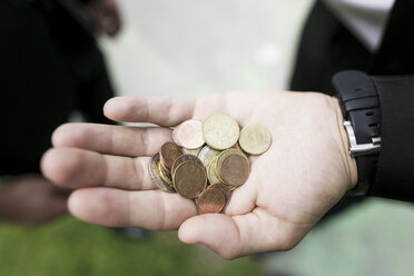 Euro coins in the hand of a businessman - KMKF00382
