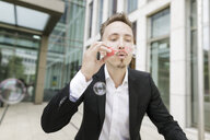 Young businessman blowing soap bubbles outdoors - KMKF00388