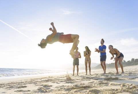 Group of friends on beach watching friend do somersault - ISF12672