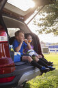 Boy and younger sister sitting in car boot eating oranges on football practice break - ISF12681