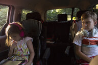 Boy watching younger sister using digital tablet in car back seat - ISF12687