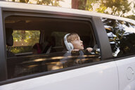 Boy wearing headphones gazing out of car window - ISF12690