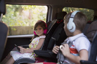 Boy and younger sister wearing headphones and using digital tablet in car back seat - ISF12693