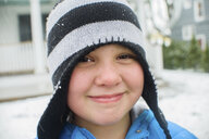 Close up portrait of girl wearing black and white striped hat in snowy garden - ISF12702