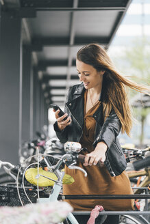Smiling young woman with bicycle using cell phone in the city - KNSF03988