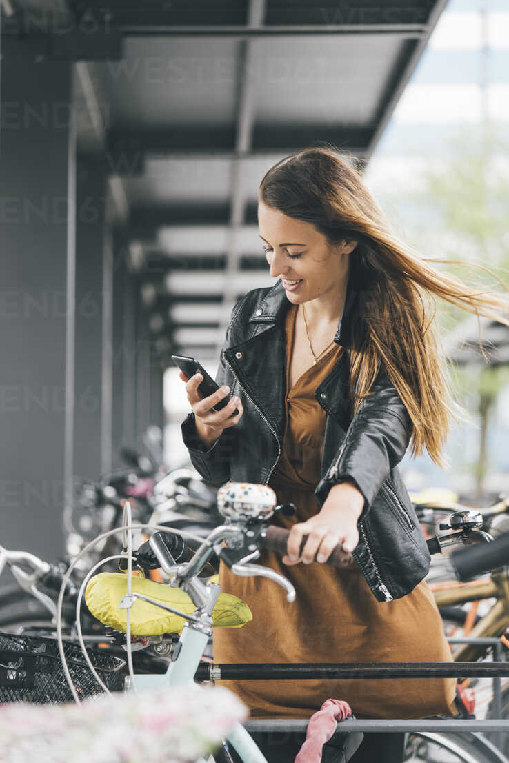 Smiling young woman with bicycle using cell phone in the city - KNSF03988 - Kniel Synnatzschke/Westend61