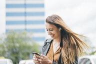Happy young woman with windswept hair using cell phone in the city - KNSF03994