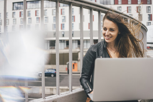 Happy young woman with windswept hair using laptop on motorway bridge - KNSF04000