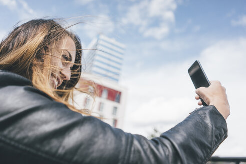 Smiling young woman taking a selfie outdoors - KNSF04003