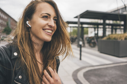 Smiling young woman wearing in-ear phones - KNSF04006
