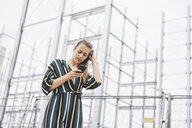 Young woman using cell phone at scaffolding - KNSF04012