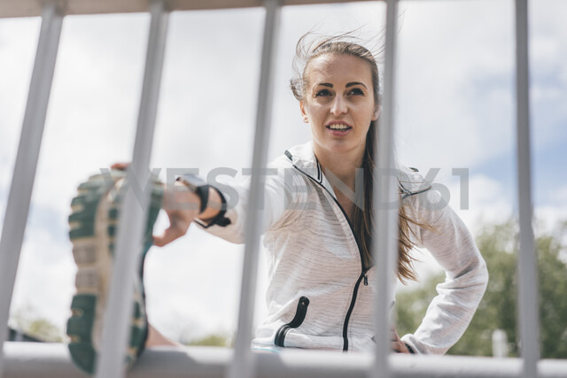 Sportive young woman stretching at railing - KNSF04021