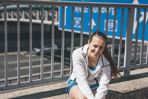 Smiling sportive young woman sitting at motorway - KNSF04024