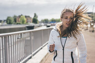 Sportive young woman with windswept hair outdoors - KNSF04030