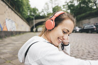 Smiling sportive young woman wearing headphones outdoors - KNSF04036