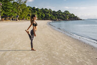 Thailand, Koh Phangan, Sportive woman doing workout on the beach - MOMF00464