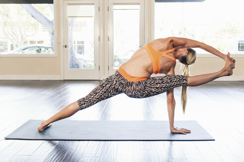 Mid adult woman in yoga position holding leg - ISF12885