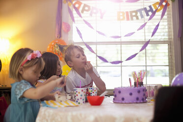 Three children sitting at table eating purple birthday cake - ISF12900
