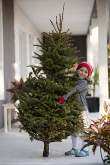 Girl carrying a christmas tree - ISF12909