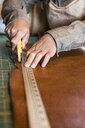 Hands of leather craftsman using rotary cutter on workshop bench - ISF12915