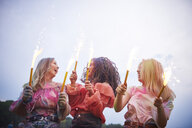 Friends with sparklers dancing at music festival - ABIF00635