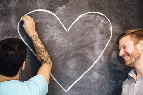 Male couple drawing heart on blackboard - ISF13032
