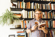 Mid adult man, standing in front of bookshelf, reading - ISF13035