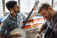 Male couple at home, play guitar and banjo - ISF13038