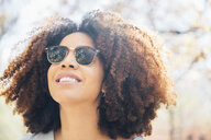 Close up portrait of mid adult woman, wearing sunglasses, smiling, looking away - ISF13061
