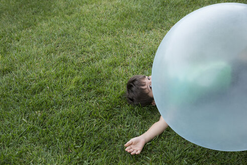 Young boy lying under large inflatable ball - ISF13073