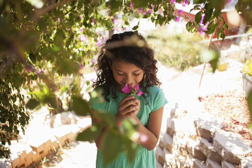 Portrait of girl in garden smelling pink blossom - ISF13172