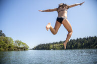 Rear view of young woman jumping into Lake Oswego, Oregon, USA - ISF13196