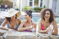 Three adult sisters wearing bikini tops chatting in garden - ISF13217
